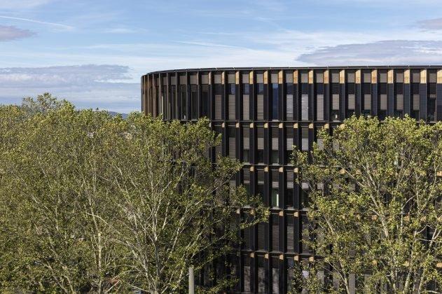 Gut zu erkennen sind die Photovoltaik-Module auf den hölzernen Fassadenelementen. Bild: HGEsch.